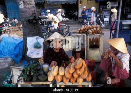 Asia Vietnam Hoi An Woman sells freshly baked baguettes in crowded Central Market along Thu Bon River - Stock Photo