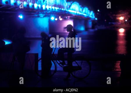 Asia Vietnam Hue Silhouette of people at base of Trang Tien Bridge Bridge across Perfume River in rain at night - Stock Photo