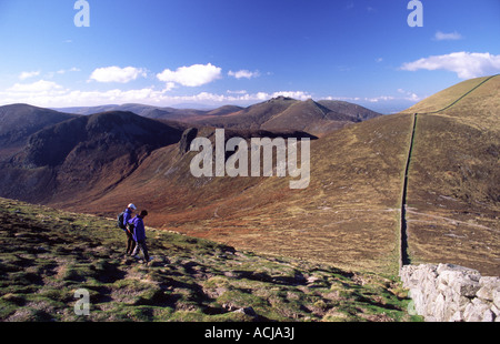 Walkers on the slopes of Slieve Donard, beside the Mourne Wall, County Down, Northern Ireland. - Stock Photo