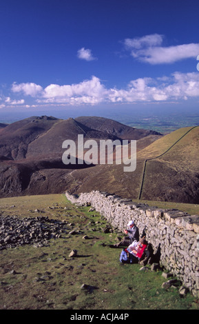 Walkers resting beside the Mourne Wall at the summit of Slieve Donard, Mourne Mountains, County Down, Northern Ireland. - Stock Photo