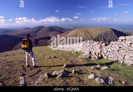 Walker looking over the Mourne Mountains from the summit of Slieve Donard. County Down, Northern Ireland. - Stock Photo