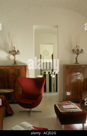 Red velvet armchairs and benches buffet candlesticks white walls - Stock Photo