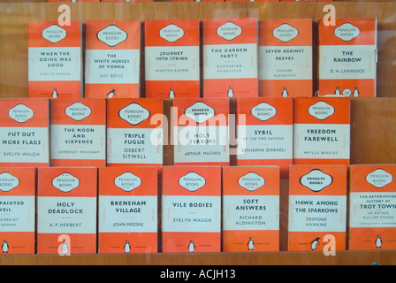 Display of old orange covered Penguin books in secondhand bookshop window - Stock Photo