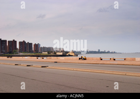 The coastal walk with the city skyline and two people sitting relaxing on folding chairs along the water. along - Stock Photo