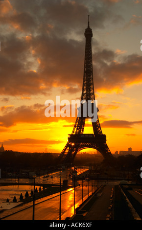 The Eiffel Tower in Paris in early morning dawn with the sun rising on the horizon, pale blue sky some white clouds - Stock Photo