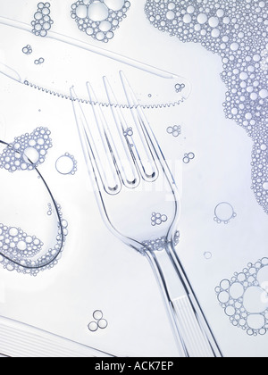 Clear Plastic Fork Knife Spoon In Clean Dish Washer Soap Water With Bubbles - Stock Photo