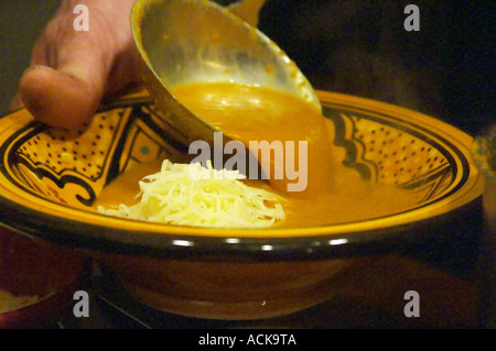 Provencal Soupe de poisson de roche, rock fish soup with grated cheese being served in a bowl, often served with - Stock Photo