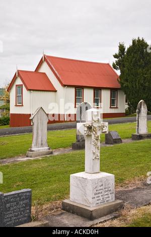 The Kauri Museum original pioneer church 1867 grave yard with ornate old stone cross headstone Matakohe Northland - Stock Photo