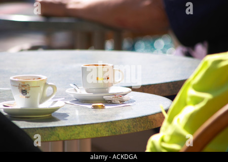 Cafe table with a cup of espresso coffee and a cup of tea and some small change coins on the table Sanary Var Cote - Stock Photo