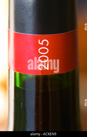 Detail of red and black neck label with the vintage year 2005 in white letters vertically Madiran France - Stock Photo