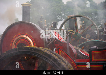 Steam engine rally - showing smoking fly-wheels soon after engines started, Scotland. - Stock Photo
