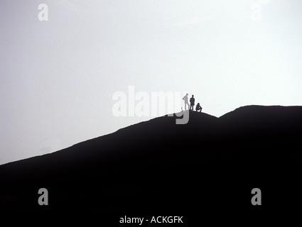 Three Climber Hikers Silhouette On Mountain Top, Ayers Rock Australia - Stock Photo