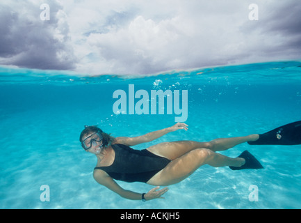 Under over view of woman snorkeling in shallow water at Northwest Point Providenciales Provo Turks Caicos Islands - Stock Photo