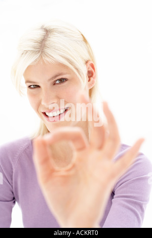 A young woman making a hand signal - Stock Photo