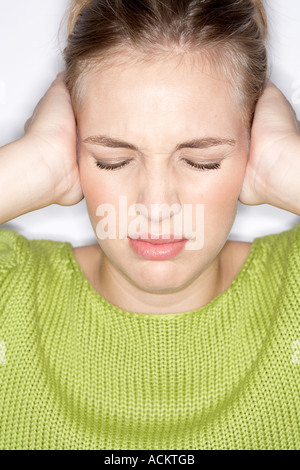 A young woman covering her ears - Stock Photo