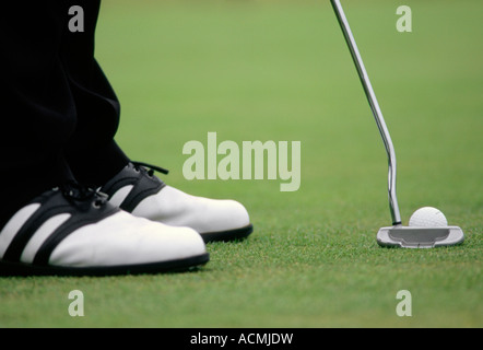 A close up of a golfers shoes putter and ball on an english golf course in the summer - Stock Photo