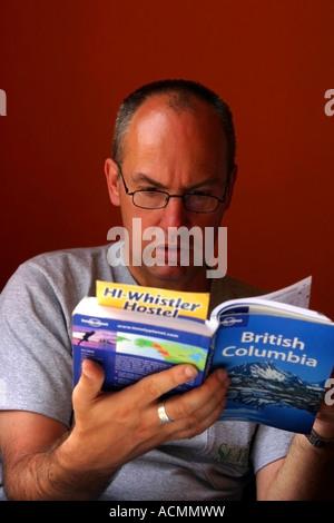 Man Reading travel book British Columbia - Stock Photo