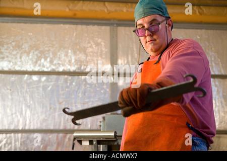 portrait of metal fabricator,blacksmith in his studio - Stock Photo