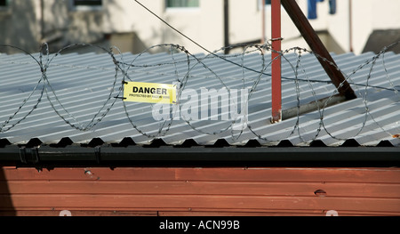A Danger Protected By Razor Wire Sign On The Edge Of The