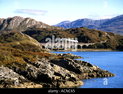 Steam train from Mallaig to Fort William passes over the Loch nan Uamh viaduct south of Arisaig - Stock Photo