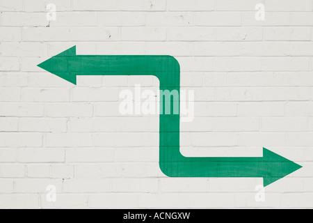 Bi-directional arrow painted on white brick wall - Stock Photo