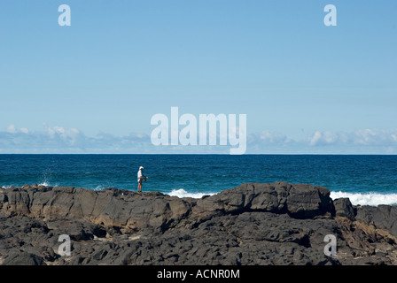 a single person standing and fishing on the rocks - Stock Photo