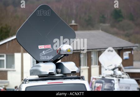 Television satellite vans at news event UK - Stock Photo