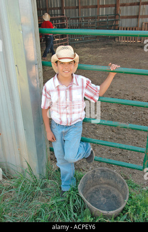 Very young ranch hand sone of cowboy at barn fence during roundup with western hat on dude ranch in Georgia mountains - Stock Photo