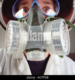 Man wearing gas mask lab protective gear respirator goggles eye protection in a bio hazard laboratory - Stock Photo