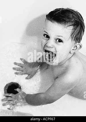 Baby boy making funny face in tub child in tub - Stock Photo