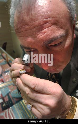 Jeweler examining a ring diamond up close using a magnifying glass - Stock Photo