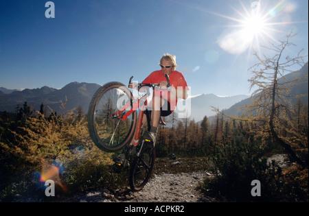 Austria, alps, man mountain biking, low angle view - Stock Photo