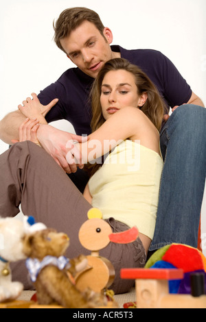 Young couple sitting on floor with toys, close-up - Stock Photo