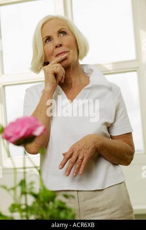 Senior woman holding finger on lips, looking away, portrait - Stock Photo