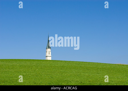 rural scene with church tower behind a green hill near Ebersberg Upper Bavaria Germany Europe - Stock Photo