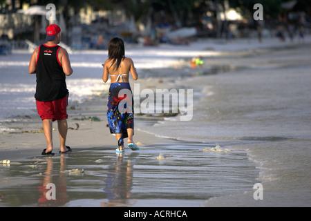 Couple walk on beach Ko Samet Thailand - Stock Photo