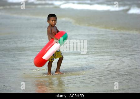 Boy with fun flotation ring in shallow water at beach Ko Samet Thailand - Stock Photo