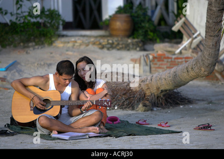 Young man plays acoustic guitar on beach as young woman looks on Ko Chang Thailand - Stock Photo
