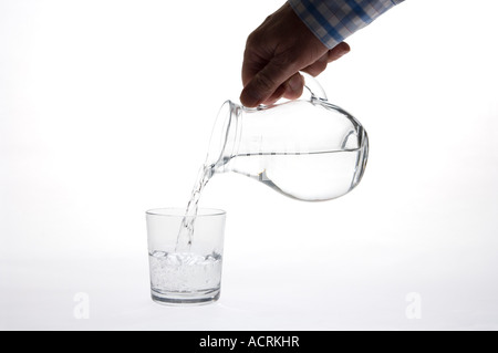 Pure clean drinking water being poured from a jug into a glass (small jug & glass) - Stock Photo
