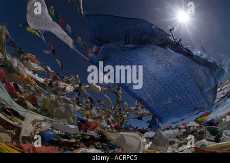 Prayer flags flutter under a Tibetan sun atop the Tsong La Pass, Tibet, China - Stock Photo