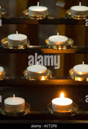 Single Church Candle Burning Amongst a Multitude of Others - Stock Photo
