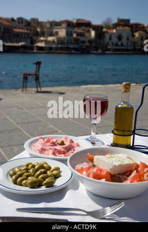 Greek Food and Drink Salad with Feta cheese Taramasalata Green Olives Olive Oil and Glass of Red Wine Chania Harbour - Stock Photo