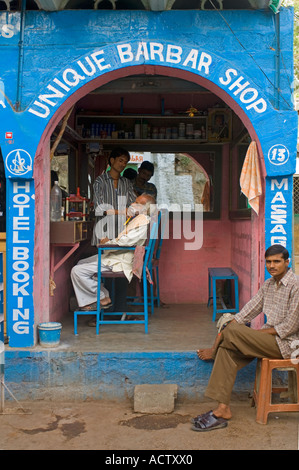 View of a barber shop in Orchha with a local man being shaved and one waiting outside. - Stock Photo