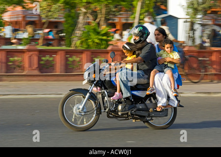 An Indian family of 4 on a motorbike and no crash helmets in a typical street scene in Jaipur with panning for motion - Stock Photo