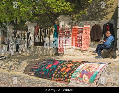 Embroidered and woven textiles and carpets kilim for sale at Andriyvsky uzviz market Kiev Kyiv Ukraine - Stock Photo