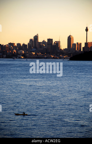 MAN IN BOAT ROWING THROUGH ELIZABETH BAY WITH SYDNEY CITY CBD IN THE BACKGROUND AT SUNSET AUSTRALIA - Stock Photo