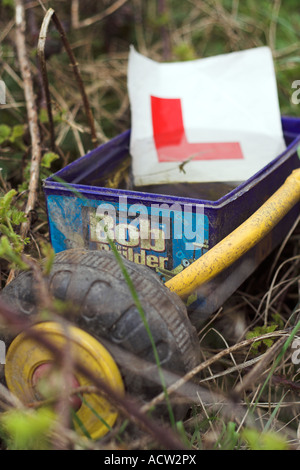 In a field, the back of a dirty discarded toddlers trike filled with water, an abandoned 'L plate' from a car attached. - Stock Photo