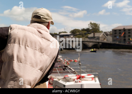 rear view of a man looking at boats on the River Teifi (Tivy) Cardigan town (Aberteifi) west  wales - Stock Photo