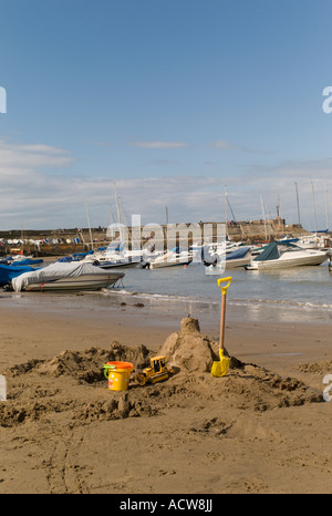 A child's sandcastle bucket and spade on New Quay beach Cardigan Bay west wales with boats moored in the harbour - Stock Photo