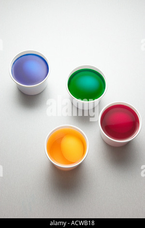 Eggs in cups of paint - Stock Photo